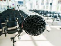 Microfone dinâmico preto no fundo da audiência sem povos Fundo borrado imagem de stock