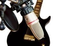 Microfone do estúdio de gravação com guitarra preta imagem de stock