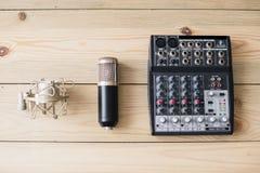 Microfone do portátil do estúdio e console de mistura no fundo de madeira imagens de stock royalty free