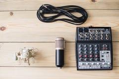Microfone do portátil do estúdio e console de mistura no fundo de madeira fotografia de stock