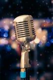 Microfone em um fundo de luzes azuis Imagens de Stock