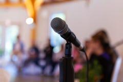 Microfone em um suporte reto, com os especialistas obscuros que dão uma conferência fotografia de stock royalty free