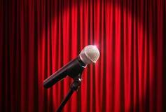 Microfone na fase contra um fundo da cortina vermelha Imagens de Stock Royalty Free