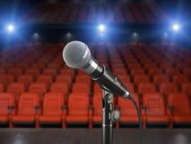 Microfone na fase da sala de concertos ou do teatro com assento vermelho Fotos de Stock