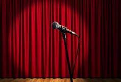Microfone na fase sob projetores com cortina vermelha Fotos de Stock Royalty Free