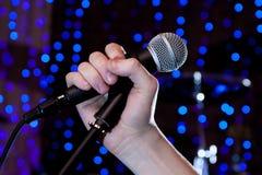 Microfone no cantor da mão Imagem de Stock Royalty Free