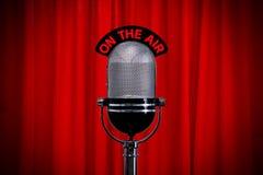 Microfone no estágio com o projector na cortina vermelha Fotografia de Stock Royalty Free