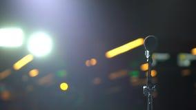 Microfone no suporte na fase do bokeh das luzes no fundo, auditório, close-up, desempenhos de espera seminário filme