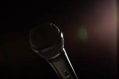 Microfone preto do estúdio em um fundo escuro imagens de stock royalty free