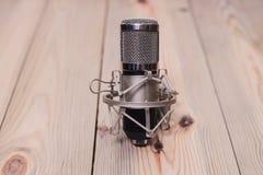 Microfone retro montado em uma plataforma de madeira com um volume de fotos de stock