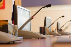 Microfones em uma tabela em uma sala de reuniões contra um fundo de monitores do computador fotografia de stock