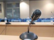 Microfoni di conferenza in un fondo vago della sala riunioni fotografia stock