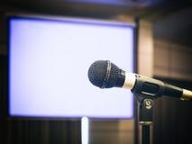 Microfono con l'evento di seminario di conferenza del fondo di schermo in bianco Immagine Stock Libera da Diritti
