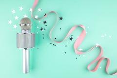 Microfono con un nastro rosa su un fondo verde con i coriandoli immagini stock