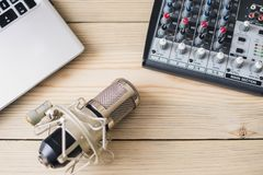 Microfono del computer portatile dello studio e console mescolantesi su fondo di legno immagini stock libere da diritti