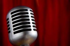 Microfono dell'annata davanti alla tenda rossa Immagini Stock