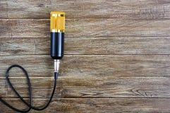 Microfono dell'oro del condensatore con le bugie del cavo su una tavola di legno con lo spazio della copia Tema musicale Disposiz immagini stock
