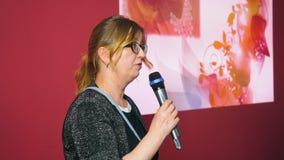 Microfono della tenuta della donna adulta e parlare sulla fase di prestazione all'evento video d archivio