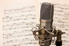 Microfono dello studio con uno strato dello spartito di musica nei precedenti fotografia stock