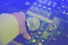 Microfono a disposizione e regolare un audio regolatore del miscelatore nella c fotografia stock libera da diritti