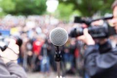 Microfono a fuoco alla protesta della via, al cineoperatore vago ed al fotografo nel fondo fotografia stock