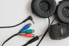 Microfono nero, cuffie nere e di spina di presa colorata multi su fondo bianco immagine stock