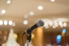 Microfoon in concertzaal of conferentieruimte met lichten in bac Stock Foto