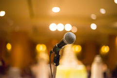 Microfoon in concertzaal of conferentieruimte met warme lichten i Stock Afbeelding