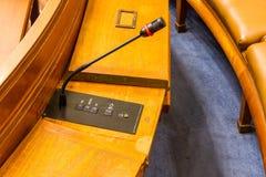 Microfoon in conferentie of raadskamer op houten bureau Stock Afbeelding