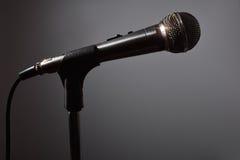 Microfoon in dark met grijze achtergrond Stock Foto