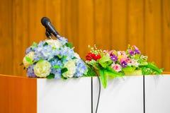 Microfoon die zich op een lijst met bloemboeket bevinden in meetin Stock Afbeeldingen