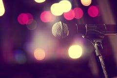 Microfoon en stadiumlichten Overleg en muziekconcept stock afbeelding