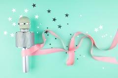 Microfoon met een roze lint op een groene achtergrond met confettien stock afbeeldingen