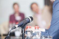 Microfoon in nadruk tegen vage mensen bij ronde tafelgebeurtenis Royalty-vrije Stock Afbeeldingen