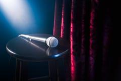 Microfoon op een houten kruk op een tribune op komediestadium met reflectorsstraal, hoog contrastbeeld royalty-vrije stock foto's