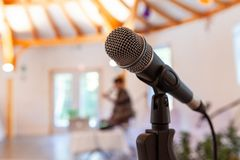 Microfoon op een rechte tribune, met onscherpe vrouw die een conferentie geven stock foto