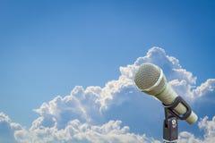 Microfoon op een tribune over vage bewolkte blauwe hemel Royalty-vrije Stock Afbeeldingen