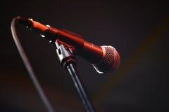 Microfoon op het stadium in rood licht op een muziekoverleg, donkere bedelaars Stock Foto