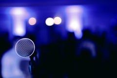Microfoon op stadium vóór het overleg op blauwe vage achtergrond royalty-vrije stock foto's