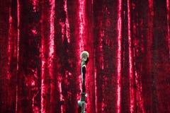 Microfoon op tribune op rode gordijnachtergrond stock foto