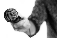 Microfoon in zingende mensenhand die wordt geïsoleerd Stock Afbeelding