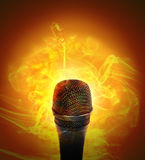 Hot Music Microphone Burning. A microhone has fire smoke around it on an orange background for a music or entertainment concept Royalty Free Stock Photos