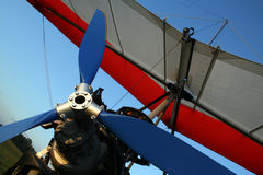 Microlight aircraft. Red and white microlight with blue propellor before flight Royalty Free Stock Image