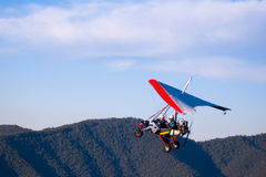 Microlight aircraft ascending. Microlight aircraft with red-edged sail ascending over the Australian Alps Stock Photo