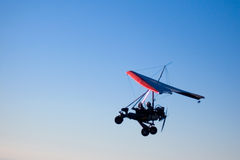 Microlight aircraft in silhouette. Microlight aircraft with red-edged sail silhouetted against evening sky Royalty Free Stock Photography