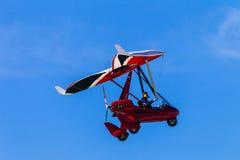 Microlight Flugzeug-Pilotblauer Himmel-Rot Stockbilder