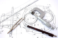 Micrometer, compass, ruler and pencil on blueprint.  royalty free stock image