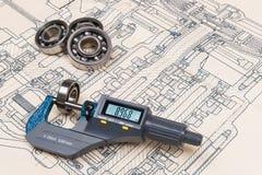 Micrometer screw gauge. Ball bearings. Drawing on background. Accurate measuring tool. Digital display. Round metal parts group. Engineering draft, plan, design stock photos