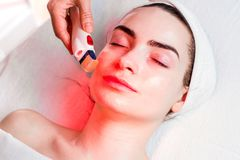Microneedle facial mesotherapy with red light Stock Photos