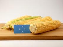 Micronesian flaga na drewnianym panelu z kukurudzą odizolowywającą na bielu zdjęcia stock